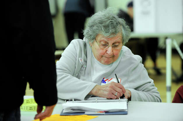 Gloria Cipolla checks names of voters as they arrive at the Huckleberry Hill Elementary School polling place in Brookfield on Election Day, Tuesday, Nov. 6, 2012. Photo: Carol Kaliff / The News-Times