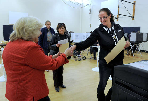 Poll worker Cathy Duggan, left, congratulates first-time voter, Elizabeth Owen, 18, as she casts her ballot at the Huckleberry Hill Elementary School polling place in Brookfield, uesday, Nov. 6, 2012. Photo: Carol Kaliff / The News-Times