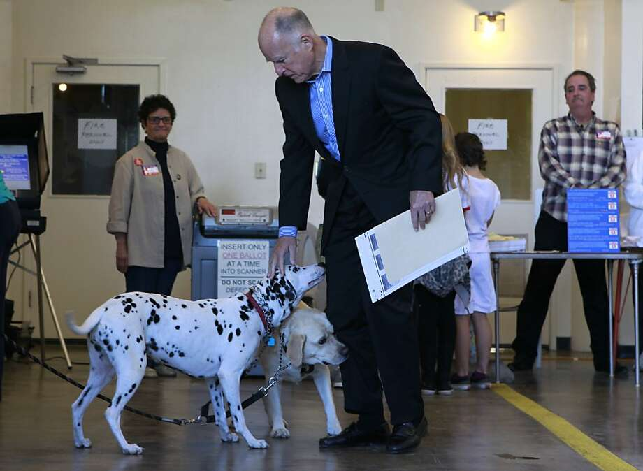 Gov. Jerry Brown pets Emma the Dalmatian and Lulu the Labrador before he casts his ballot in Oakland, Calif. on Tuesday, Nov. 6, 2012. Photo: Paul Chinn, The Chronicle