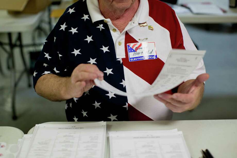 PACIFIC, MO - NOVEMBER 6:  Election judge George Barfield hands out ballots to voters as they arrive at the Pacific Eagles Club in Pacific, Missouri on November 6, 2012. As Americans go to vote, U.S. President Barack Obama and Republican presidential candidate Mitt Romney are in a virtual tie in the national polls. Photo: Whitney Curtis, Getty Images / 2012 Getty Images