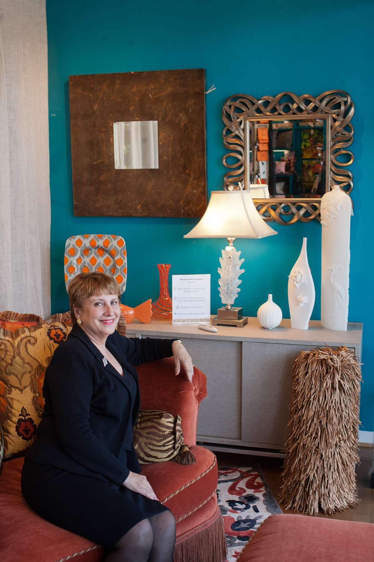 Lynne Averett on a Raymond Waites collection orange sofa at The Frog at Home's Houston showcase.