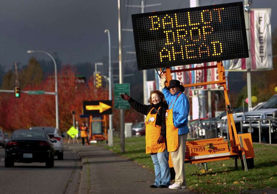 Rotary volunteers Andee Jorgensen and John Baumann wave to passing motorists as they stand under a sign advertising a ballot drop location near  the King County ballot-processing facility in Renton on Election Day. Photo: JOSHUA TRUJILLO / ASSOCIATED PRESS