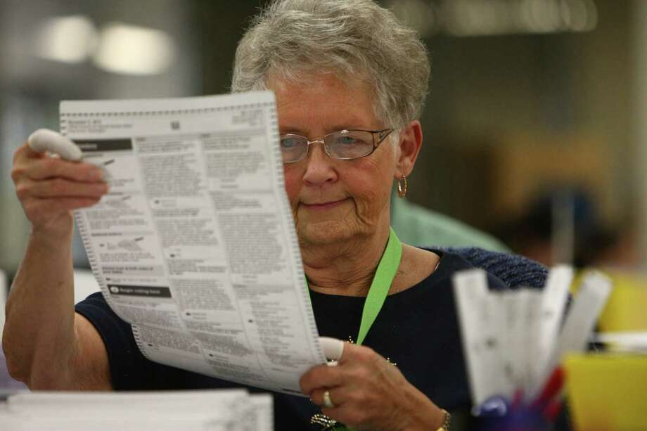 Jan Reese looks over a ballot at the King County ballot-processing facility in Renton on Election Day. Photo: JOSHUA TRUJILLO / ASSOCIATED PRESS