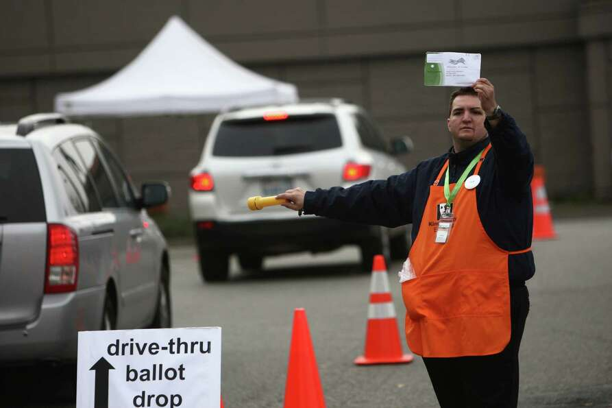 Jeffrey McGinn guides cars to a ballot drop box at the King County ballot-processing facility in Ren