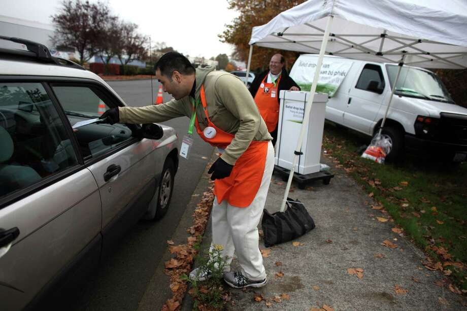 Thomas Toguchi, center, and Steven Enrich collect ballots at a drop point near the King County elections facility in Renton on Election Day. Photo: JOSHUA TRUJILLO / ASSOCIATED PRESS