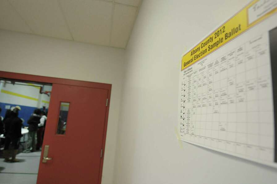 A sample ballot is seen taped to the wall outside the door to the polling station at the Community C