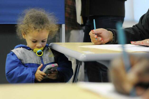 Joell-Damien Johnson, 2, plays a game on his mom's, Melissa Johnson, phone while she filled out her ballot at the polling station inside Green Tech High Charter School on Tuesday, Nov. 6, 2012 in Albany, NY.    (Paul Buckowski / Times Union) Photo: Paul Buckowski  / 00019998A