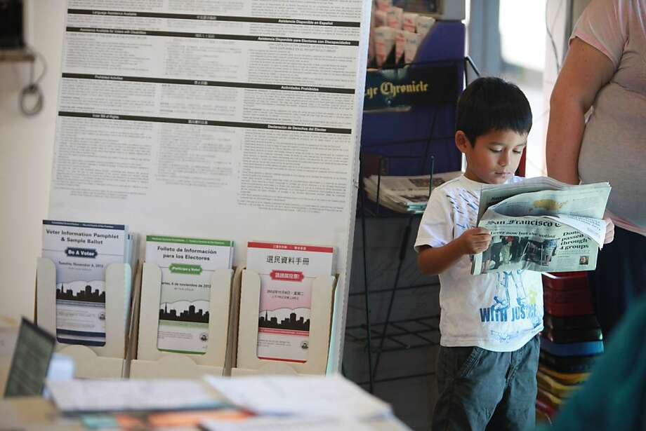 Alexis Perez, 4,  of San Francisco looks over a newspaper as he stands with his aunt next to a display containing voting information pamphlets as he waits for his mother to vote at Cordova Market and Deli on Tuesday, November 6, 2012 in San Francisco, Calif. Photo: Lea Suzuki, The Chronicle