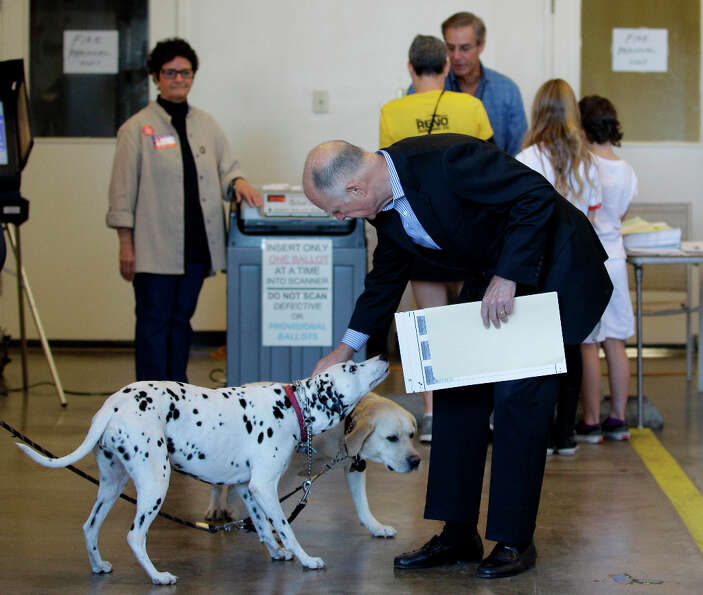 California Gov. Jerry Brown pets a Dalmatian before voting Tuesday, Nov. 6, 2012 at a fire station i