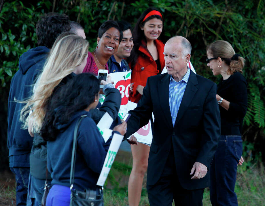 Gov. Jerry Brown greets supporters of his Prop. 30 school tax initiative before he votes in Oakland, Calif. on Tuesday, Nov. 6, 2012. Photo: Paul Chinn, The Chronicle / ONLINE_YES