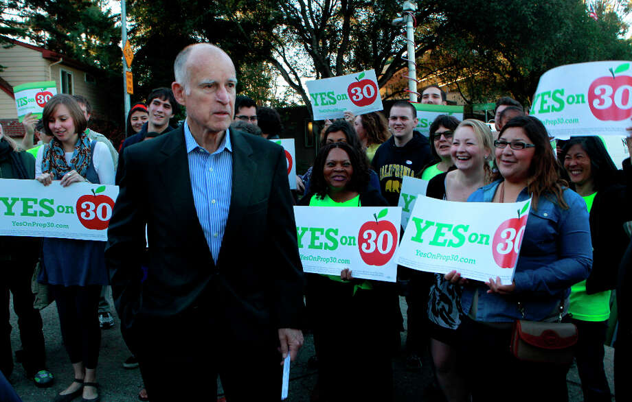 Supporters of the Prop. 30 school tax initiative rally around Jerry Brown after the governor voted near his home in Oakland, Calif. on Tuesday, Nov. 6, 2012. Photo: Paul Chinn, The Chronicle / ONLINE_YES