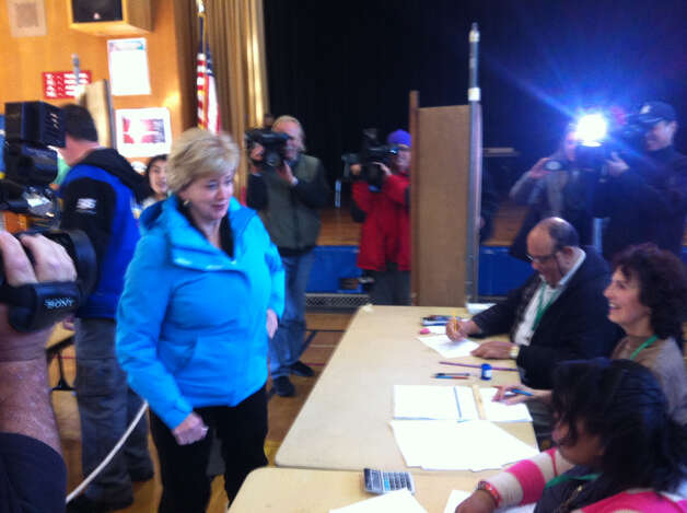 Linda McMahon asks a poll worker in jest if she needs to show identification.
