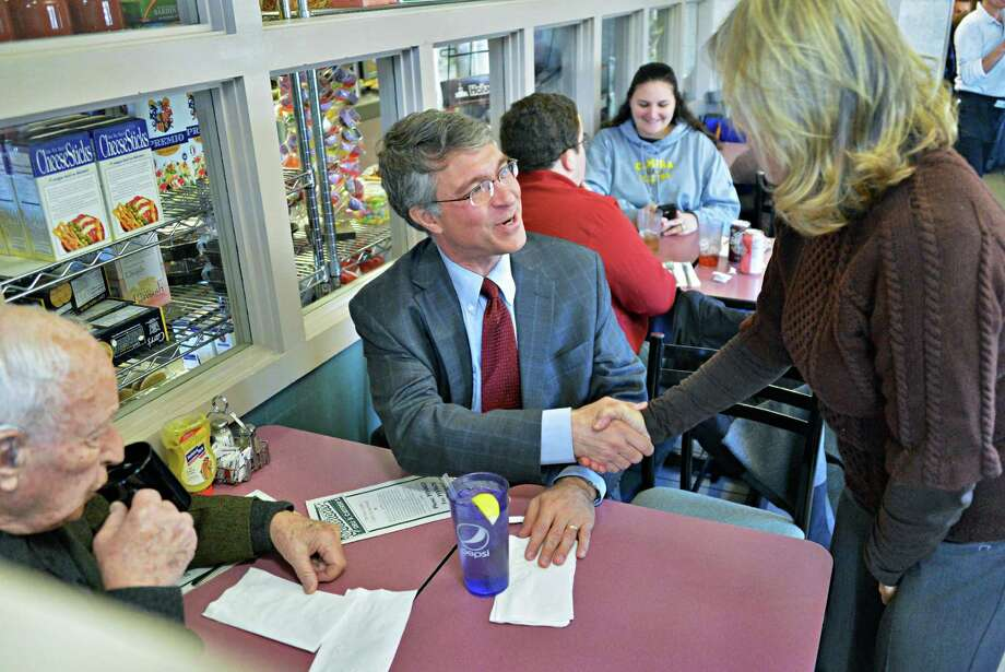 NYS Assembly candidate Phillip Steck, center, shakes hands with a well wisher as he lunches with his father Ernie Steck, at left, at Gershon's Deli in Schenectady Tuesday Nov. 6, 2012.  (John Carl D'Annibale / Times Union) Photo: John Carl D'Annibale, Albany Times Union / 00019984A