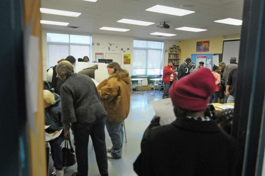 Some voters wait in line to receive their ballot as other voters fill out their ballots at the polli