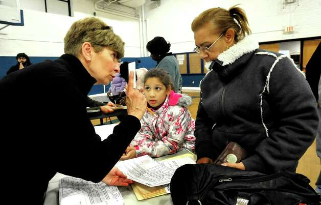 Election worker Barbara Webber, left, instructs Cyiselda Adams on voting as her daughter, Jalin Adams, 8, translates, at the Danbury War Memorial Tuesday, Nov. 6, 2012. Photo: Michael Duffy / The News-Times
