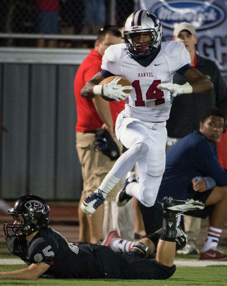 Manvel wide receiver Austin Bennett leaps over Pearland defensive back Zach Kanipes as he breaks free on a 42-yard touchdown pass last week. Photo: Smiley N. Pool, Staff / © 2012  Houston Chronicle