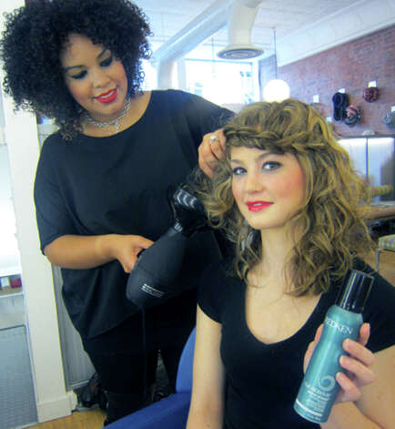 Receptionist Brooke Cassalia displays a container of a Redken curl product she uses with professional assistance from stylist Isabella Vazquez at Joe's Salon and Spa along Bank Street in the New Milford village center. November 2012 Photo: Norm Cummings