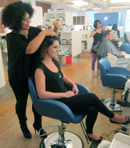Stylist Isabella Vazquez works her magic on fellow Joe's Salon & Spa staffer Alyssa Voytek at the Bank Street salon in the New Milford village center. November 2012 Photo: Norm Cummings