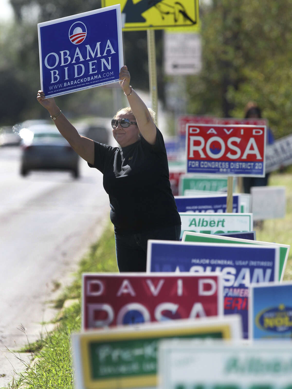 Janie Aguilar shows she's backing President Barack Obama and Vice President Joe Biden on Tuesday. She was standing in front of Ridgeview Elementary School on McCullough Avenue on Tuesday.