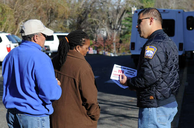 Career firefighter Jon Brenes speaks to voters outside Stillmeadow Elementary School to urge them to vote yes on Question 2 on Tuesday, November 6, 2012. Photo: Lindsay Niegelberg / Stamford Advocate