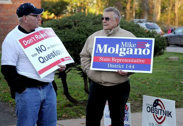 Volunteer firefighter Roy Compkinks, left, and Mike Molgano supporter Rich Gabriele, right, hold signs outside Dolan Middle School on Tuesday, November 6, 2012. Photo: Lindsay Niegelberg / Stamford Advocate