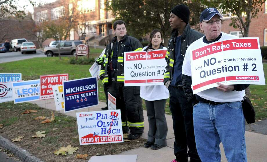 From left, volunteer firefighter Zack LaMotta, Sephanie Ruiz, and volunteer firefightesr Nick Hazel and Roy Compkins hold signs urging voters to choose no on Question 2 at Dolan Middle School on Tuesday, November 6, 2012. Photo: Lindsay Niegelberg / Stamford Advocate