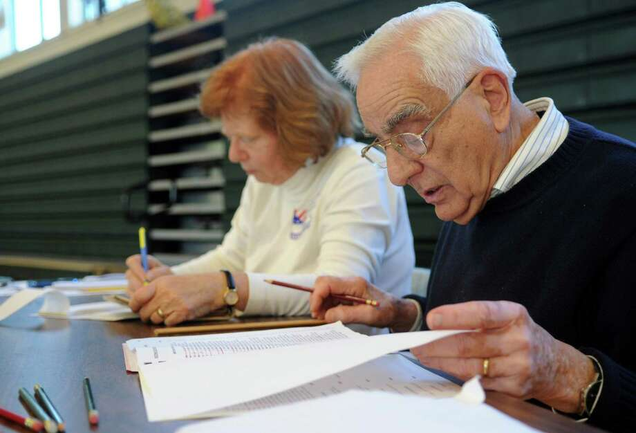 Deborah Goldberg, left, and Leonard Pensiero, right, work at the polls at Rippowam Middle School on Tuesday, November 6, 2012. Photo: Lindsay Niegelberg / Stamford Advocate