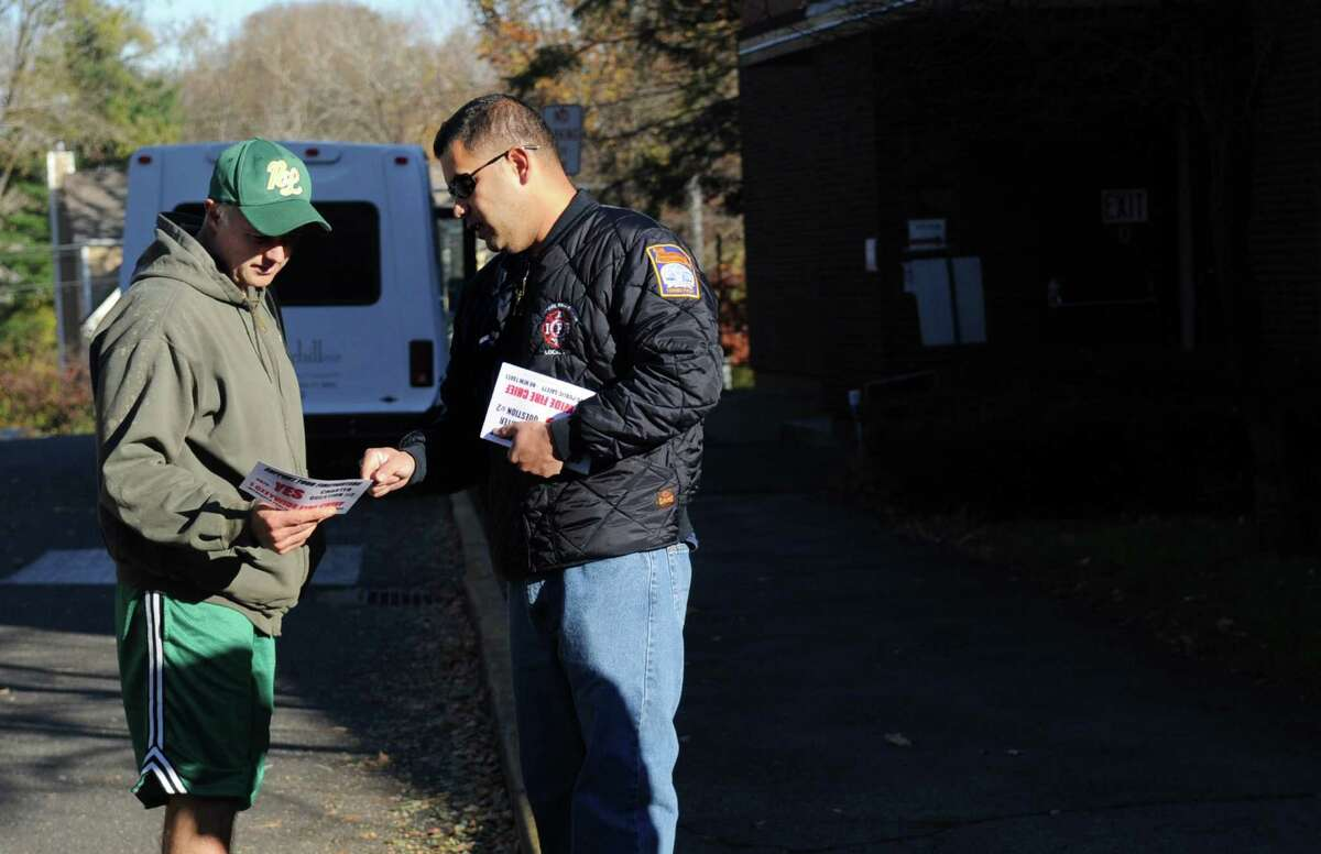 Career firefighter Jon Brenes speaks to voter Gene Edwards outside Stillmeadow Elementary School to urge him to vote yes on Question 2 on Tuesday, November 6, 2012.