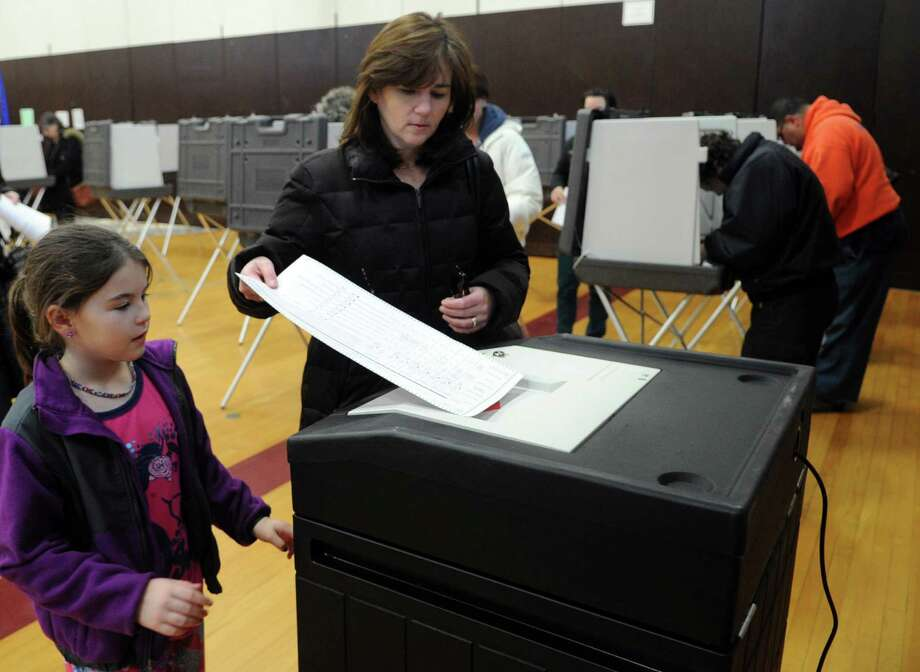 Katelyn Fleeson, 8, watches her mother, Mary, submit her ballot at Dolan Middle School on Tuesday, November 6, 2012. Photo: Lindsay Niegelberg / Stamford Advocate