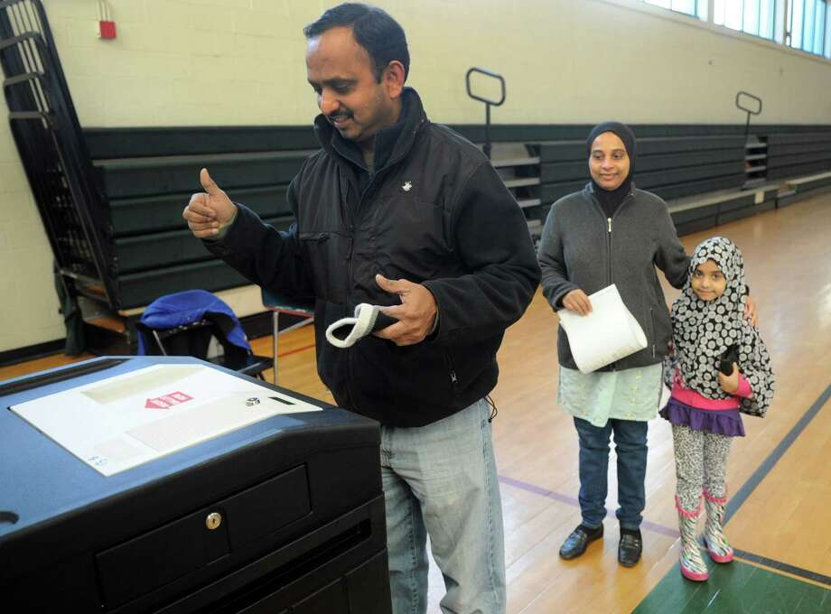 Imtiyaz Jamsu submits his ballot at Rippowam Middle School with his wife, Abeda, and daughter, Falak, 6, on Tuesday, November 6, 2012. Photo: Lindsay Niegelberg / Stamford Advocate
