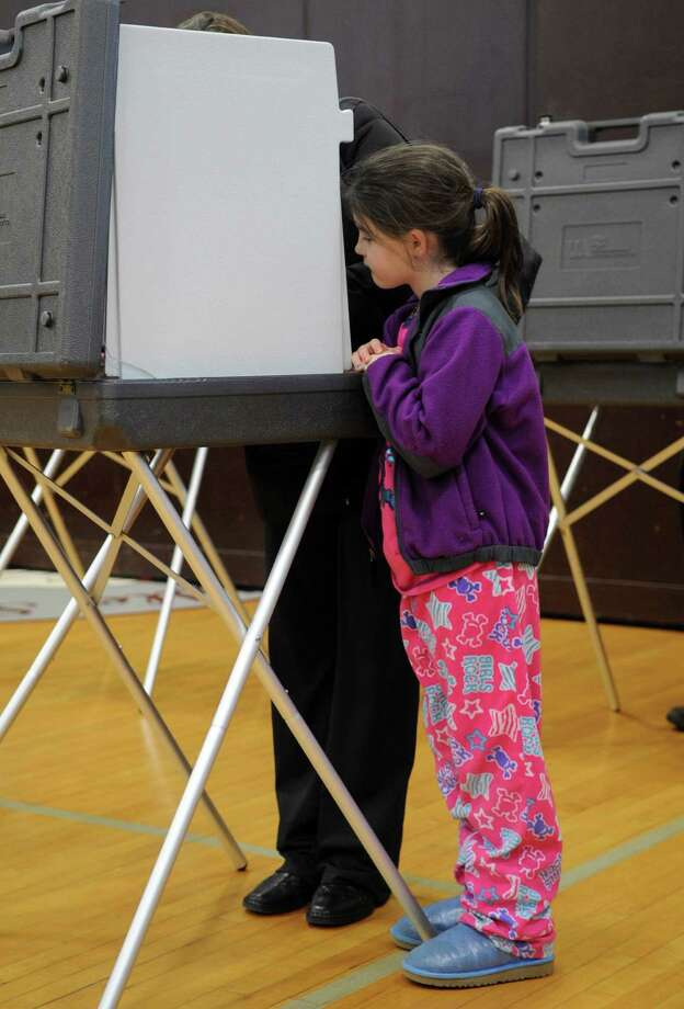 Katelyn Fleeson, 8, watches her mother, Mary, fill out a ballot at Dolan Middle School on Tuesday, November 6, 2012. Photo: Lindsay Niegelberg / Stamford Advocate