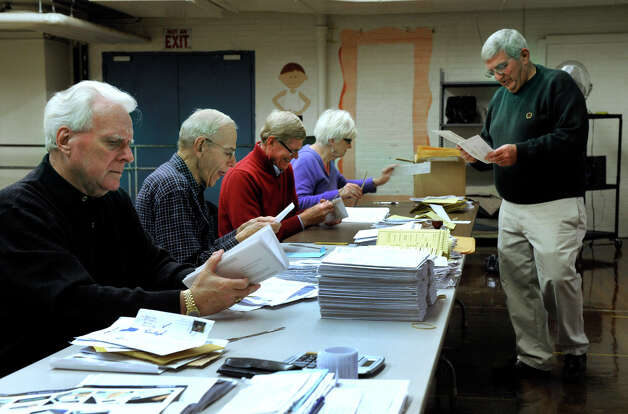 Bob DiMatteo, right, head moderator at the Bethel Municipal Center polling place, works with volunteers who are counting absentee ballots, Tuesday, Nov. 6, 2012. Photo: Carol Kaliff / The News-Times