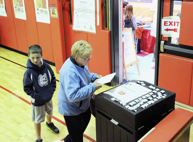 With her grandson, Alex Pica, 11, of Wilton, in tow, Joanne Fuss prepares to enter her ballot into the voting tabulation machine at New Lebanon School in Byram, Tuesday afternoon, November 6, 2012. Photo: Bob Luckey / Greenwich Time