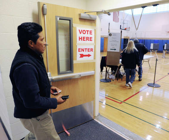 A voter carrying his identification enters the Western Middle School Gym in Byram, Tuesday afternoon, November 6, 2012, during the election. Photo: Bob Luckey / Greenwich Time