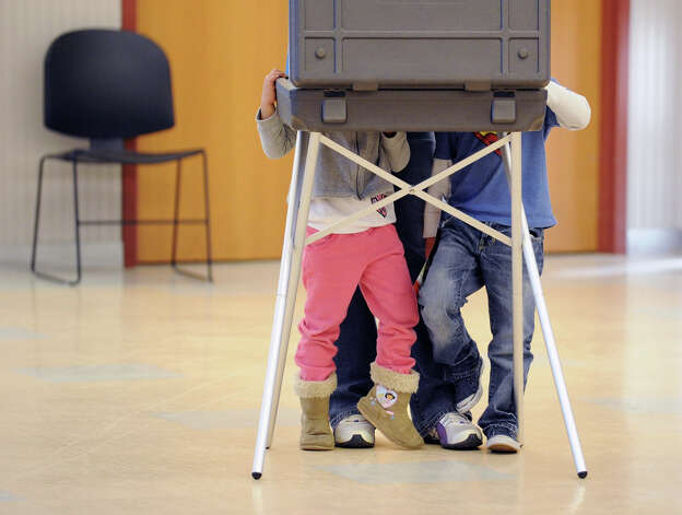 At left, Ibanna Peralta, 4, and her brother, Javier Peralta, right, 6, crowd out their mother, Marie Ramon, who was at a voting table filling in her ballot at the Western Greenwich Civic Center in Glenville, Tuesday afternoon, November 6, 2012. Photo: Bob Luckey / Greenwich Time