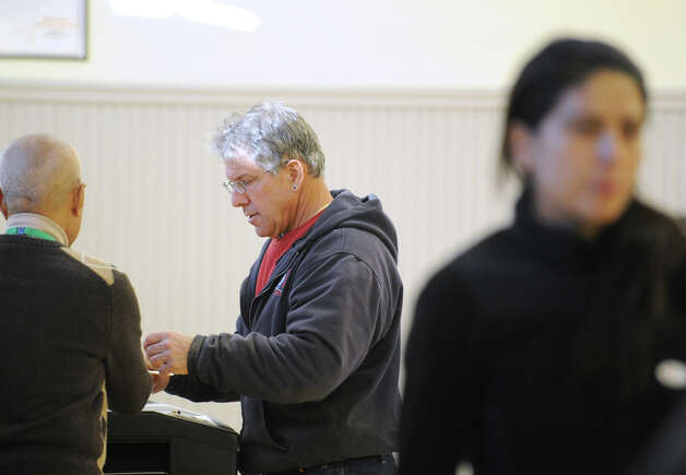 At center, Joseph Chiappetta Jr. enters his ballot into the voting tabulation machine with the help of election worker Tomas Zeta, left, at the Western Greenwich Civic Center in Glenville, Tuesday afternoon, November 6, 2012. Photo: Bob Luckey / Greenwich Time