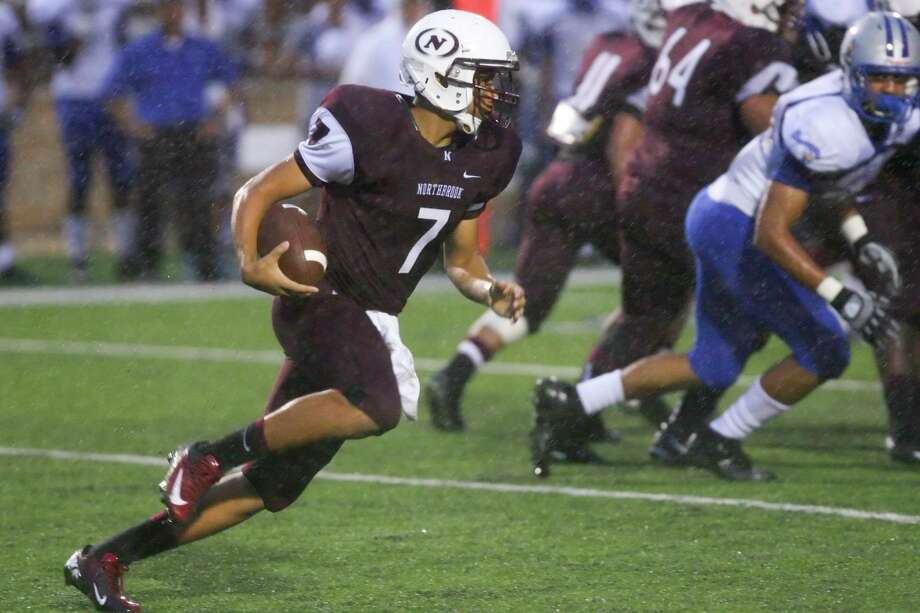 Northbrook quarterback Jacob Salazar tries to keep his footing the in heavy rain as he runs a keeper play up the middle late in the second quarter of the Willowridge game Saturday night. Photo: Matthew White, Freelance / Freelance