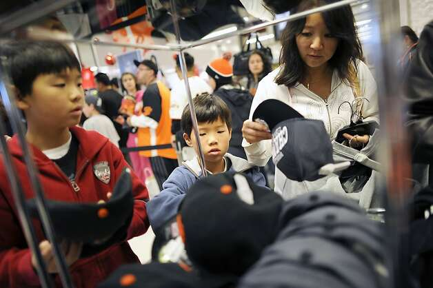 Kristine Choy of San Francisco shops for hats for her sons Ryan, 8, and Brett, 10, so they can get them signed by Angel Pagan at Macy's.  San Francisco Giants center fielder Angel Pagan was at Macy's signing autographs to kick off their sale of officially licensed Major League Baseball gear.  San Francisco, CA, November 3rd, 2012. Photo: Michael Short, Special To The Chronicle