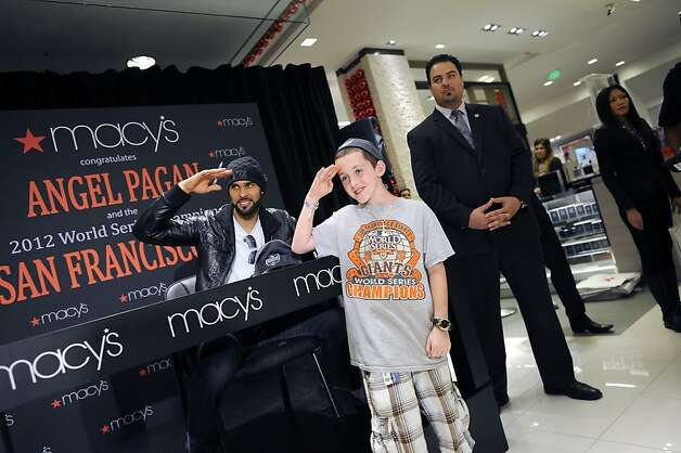 Justin Holbrook salutes along with Giants outfielder Angel Pagan at Macy's; Pagan chats with fans; the crowd takes photos while waiting; longtime Giants fan Drina Lizarraga of San Francisco; balls signed by Pagan. Photo: Michael Short, Special To The Chronicle