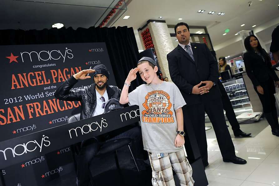 Justin Holbrook salutes along with Giants outfielder Angel Pagan at Macy's; Pagan chats with fans; t