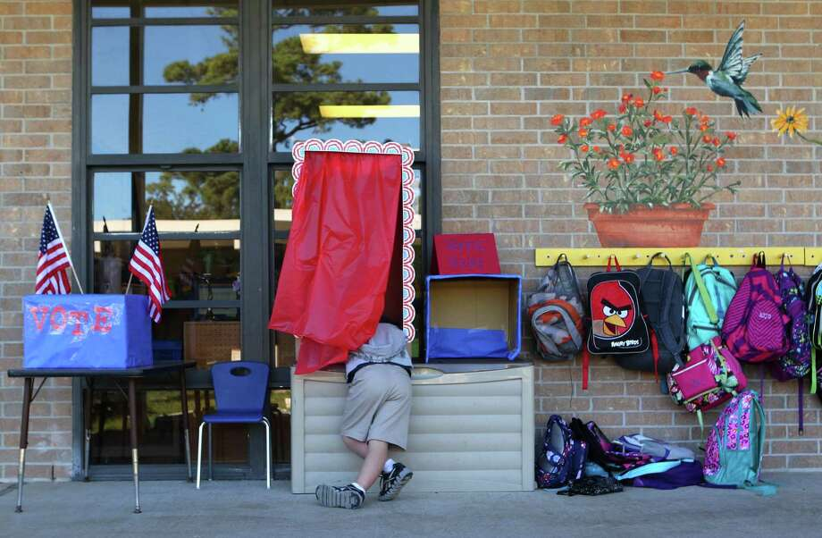 Samuel Manzalez, 6, casts his vote for or against the HISD Bond as the first through third graders in teacher Luz Torres class learned about voting as part of their social studies civic lesson at Garden Oaks Elementary School. Photo: Johnny Hanson, Houston Chronicle / © 2012  Houston Chronicle