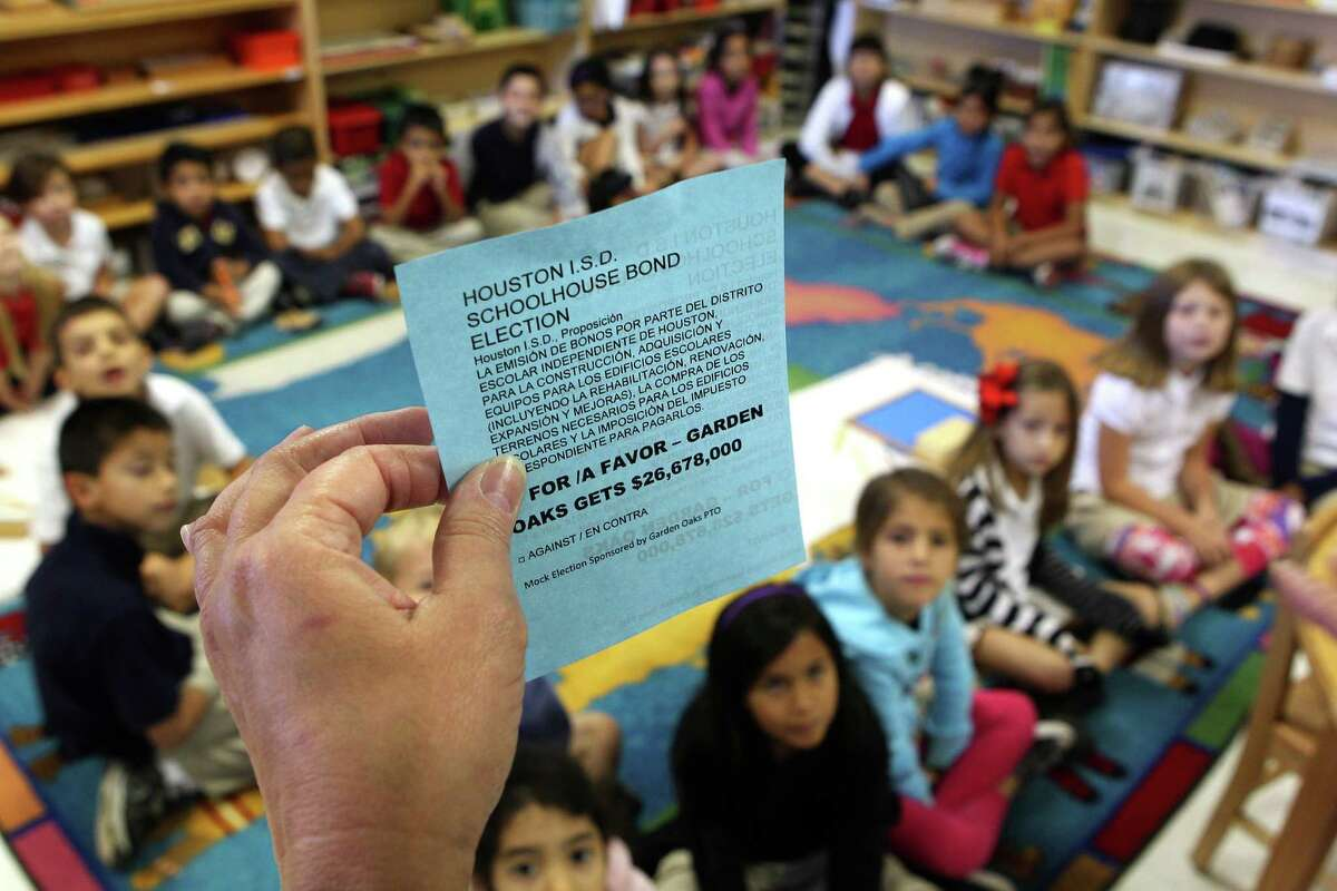 Instructional coordinator Cynthia Martin holds a sample ballot as she taught the first through third graders in teacher Luz Torres class about voting as part of their social studies civic lesson at Garden Oaks Elementary School. The students were able to cast their own vote and oppinion for or against the HISD Bond.