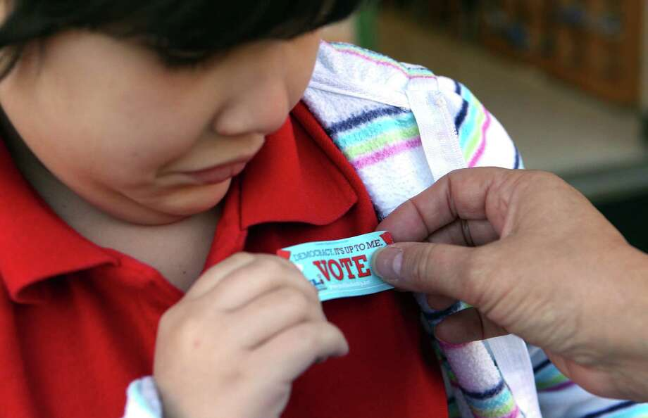 Emma Maltbie, 7, gets a sticker after she voted for or against the HISD Bond as the first through third graders in teacher Luz Torres class learned about voting as part of their social studies civic lesson at Garden Oaks Elementary School. Photo: Johnny Hanson, Houston Chronicle / © 2012  Houston Chronicle
