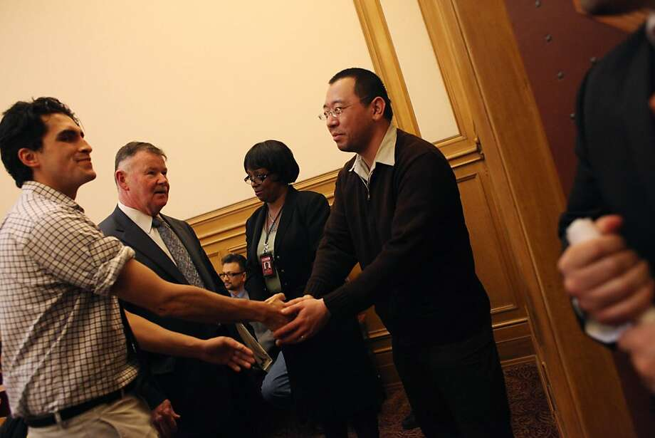 Alan Yam (right), who was driving the Muni bus that was set on fire after the Giants' World Series win, and Simon Timony (left), who tried to prevent the crowd from vandalizing the Muni bus after the Giants' World Series win, shake hands before a ceremony honoring them at City Hall on Tuesday, November 6, 2012 in San Francisco, Calif. Photo: Lea Suzuki, The Chronicle