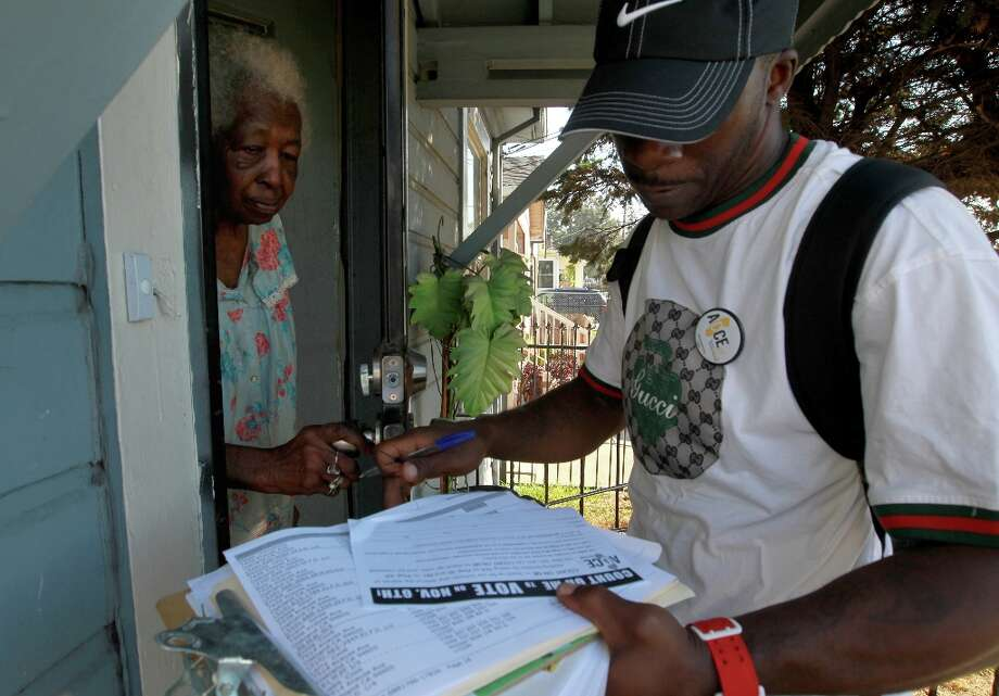 Antwan Johnson, right, with the Alliance of Californians for Community Empowerment (ACCE) talks with Erma Cook as he goes door to door to encourage people to vote, Tuesday Nov. 6, 2012, in East Oakland, Calif. Photo: Lacy Atkins, The Chronicle / ONLINE_YES