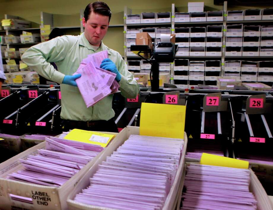 Devin Brown organizes absentee ballots before they are counted in the Department of Elections at City Hall in San Francisco, Calif. on Tuesday, Nov. 6, 2012. Photo: Paul Chinn, The Chronicle / ONLINE_YES