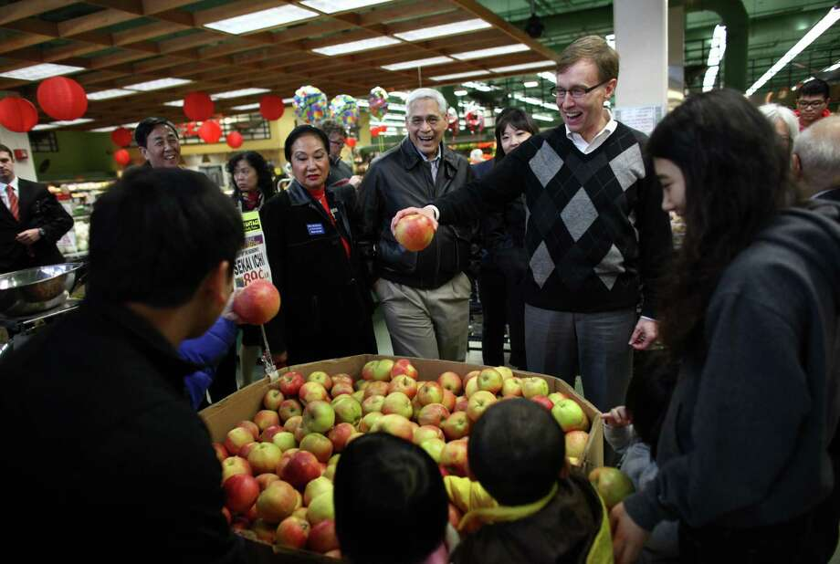 Republican candidate for Washington State Governor Rob McKenna holds up a large apple in Uwajimaya supermarket as he tours Seattle's International District with business leaders on Election Day, Tuesday, November 6, 2012. Photo: JOSHUA TRUJILLO / SEATTLEPI.COM