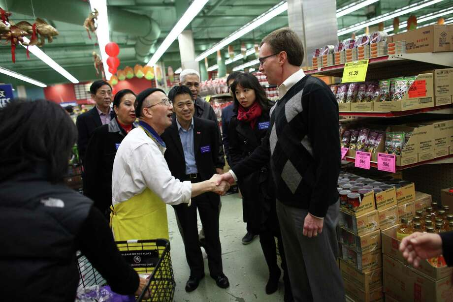 Republican candidate for Washington State Governor Rob McKenna is greeted by William Sung, who has worked in the fish market at Uwajimaya supermarket for 23 years, as McKenna tours Seattle's International District with business leaders on Election Day, Tuesday, November 6, 2012. Photo: JOSHUA TRUJILLO / SEATTLEPI.COM