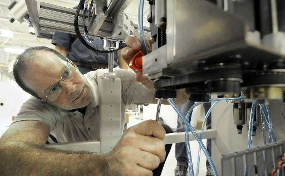 Stamford-based Pitney Bowes Inc. continues to expand its business in machines and digital products with the help of engineers like Dan Williams pictured here working in Danbury in August.Shares in Pitney Bowes rose 0.39 percent to $12.75. (News-Times file photo / Hearst Media)
