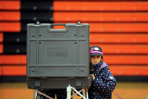 Seven-year-old Nicole Fortin stands beside the voting booth as her mother fills out her ballot Tuesday, Nov. 6, 2012 at Shelton Intermediate School in Shelton, Conn. Photo: Autumn Driscoll / Connecticut Post